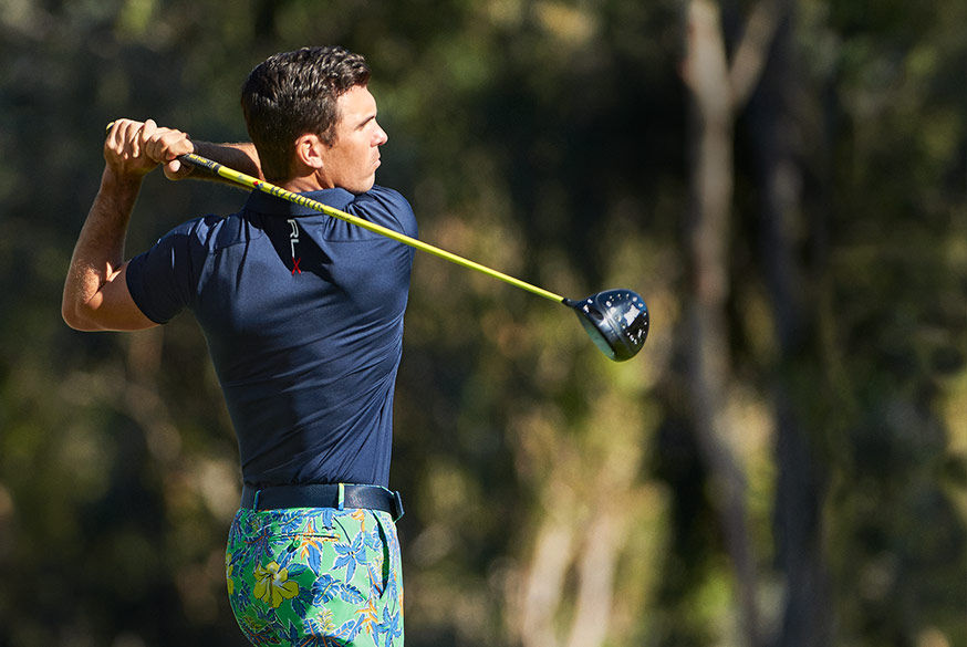 Billy Horschel, wearing blue RLX Polo shirt & floral-print pant finishes swing with his driver
