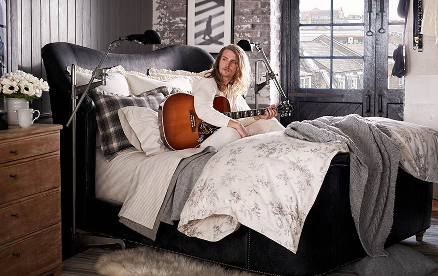 Man plays guitar in bed with sheeting in grey & white patterns