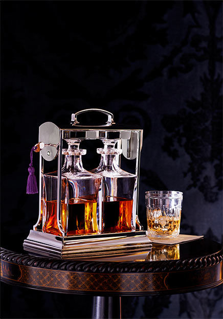 Silver caddy holds two glass decanters