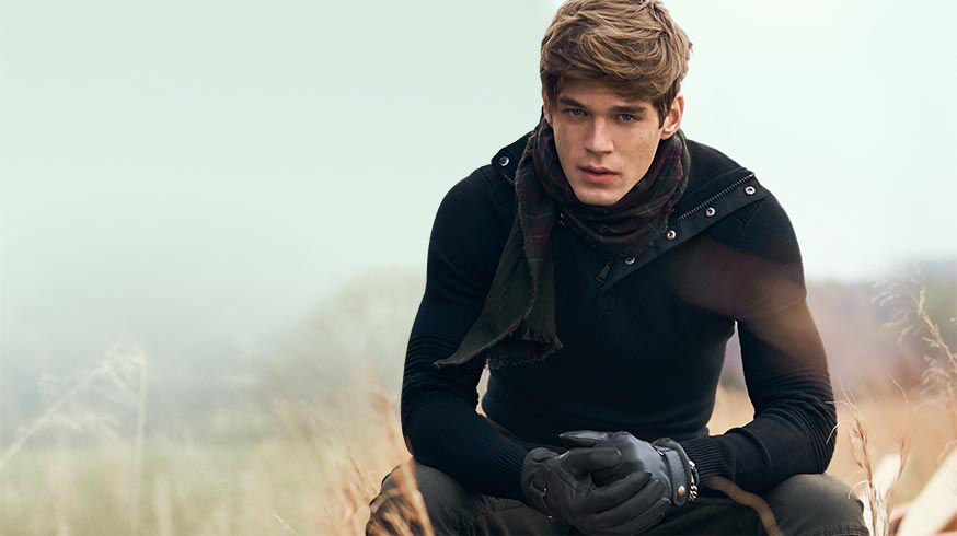 Man wears black half-zip sweater, tonal plaid scarf & leather gloves